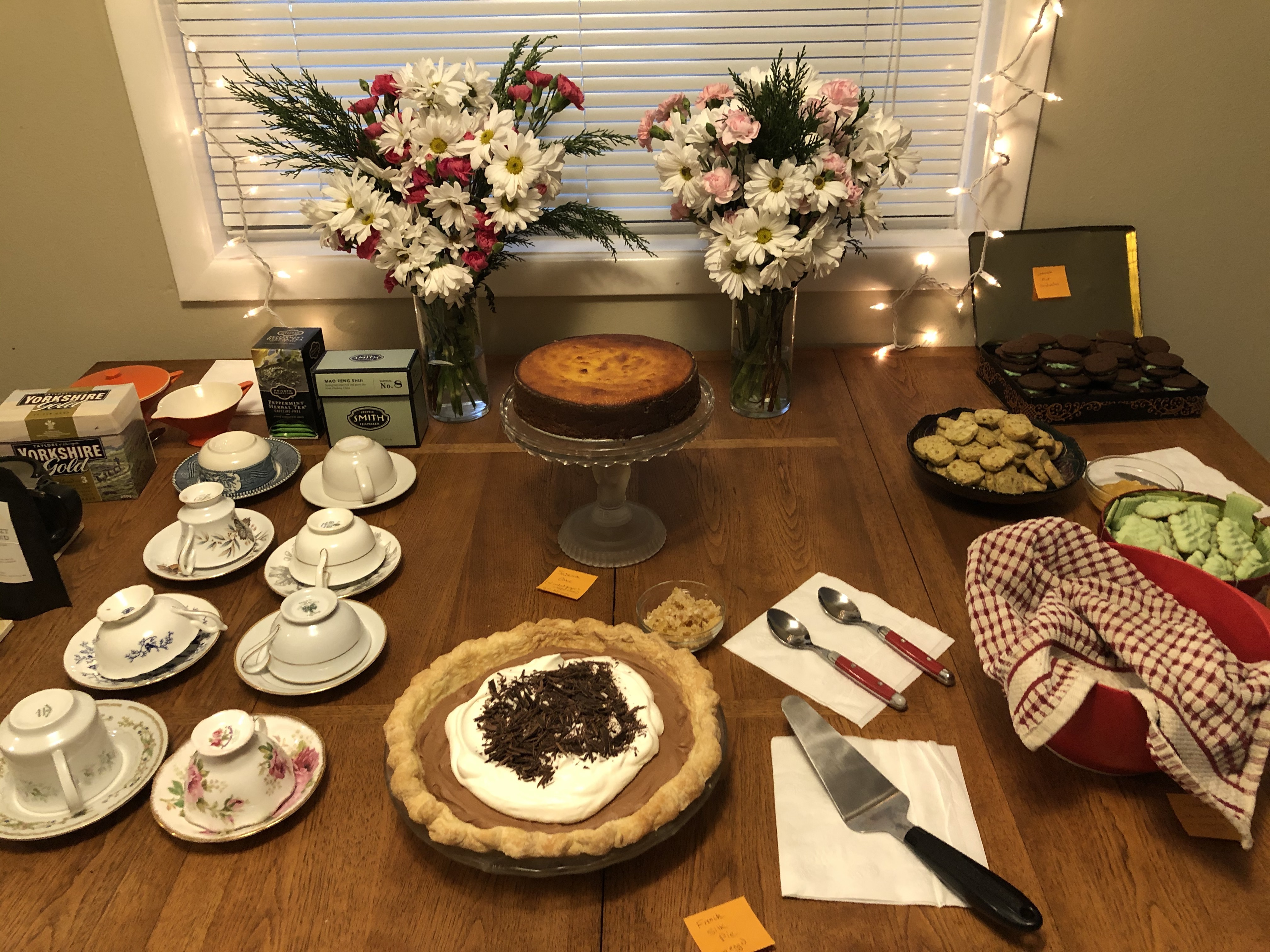 A table filled with desserts. There's an orange cake on a glass cake stand, a chocolate pie, three tins of Christmas cookies, two vases of fresh flowers, and a line-up of teacups and tea to the side.