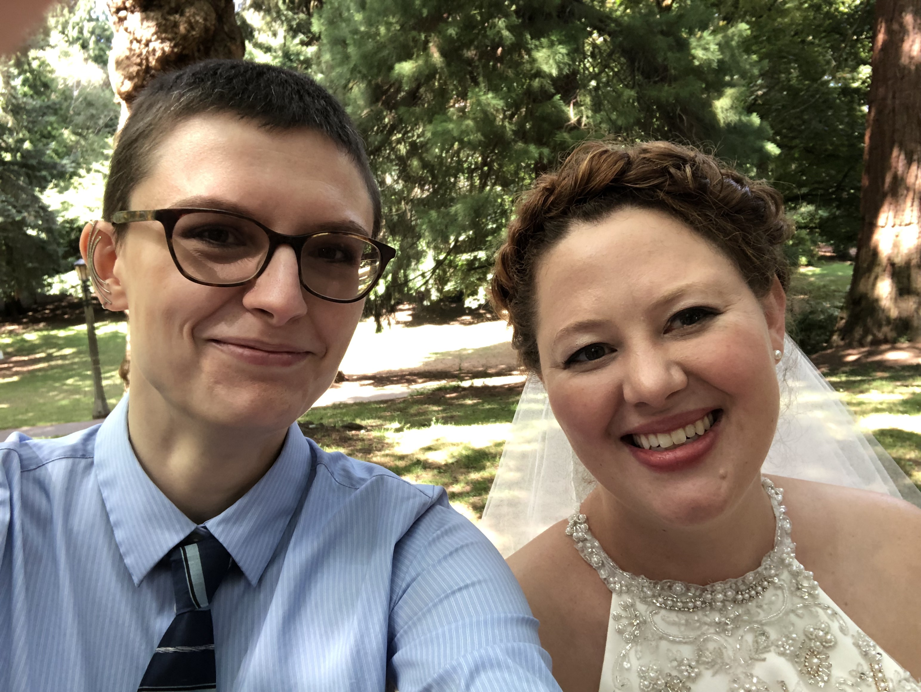 Selfie of me and my friend at her wedding. I'm wearing a blue button up shirt and tie and she's in a white bridal gown with her hair up. We are smiling.